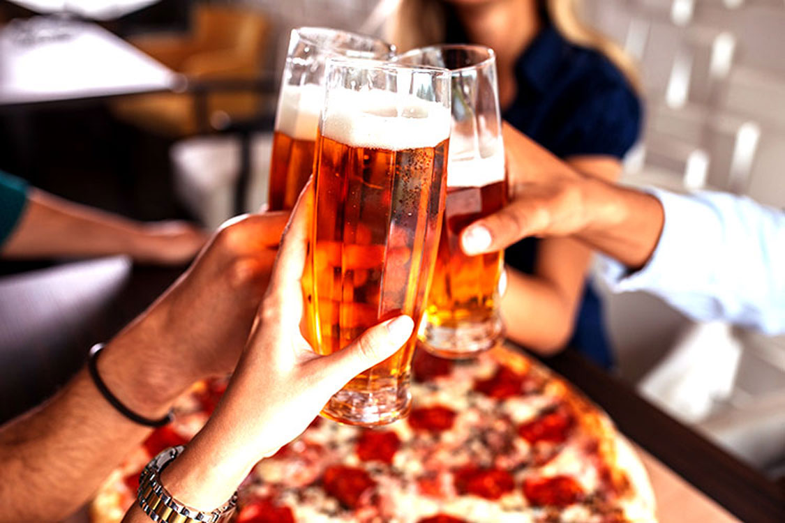group cheers with beer while eating at pizza restaurant