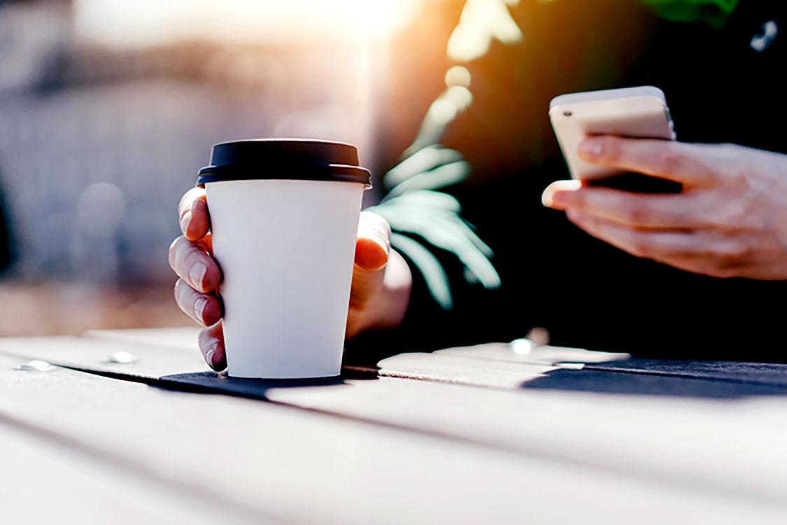 man drinking hot coffee outside using locelli app