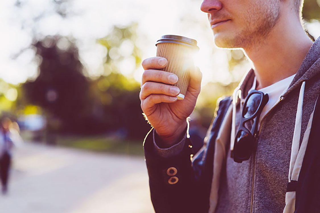 man smiling and drinking coffee on the go